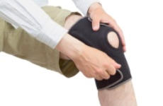 Image of a man adjusting a brace on his knee