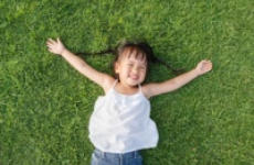 Image of little girl lying in the grass smiling